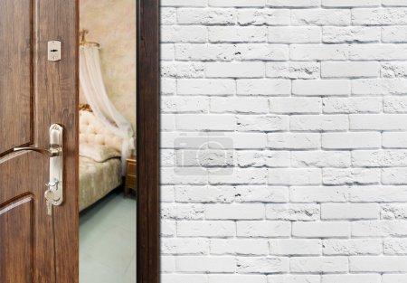 Photo pour Half opened door to a bedroom. Door handle, door lock. Lounge door half open. Opening door. Welcome, privacy concept. Entrance to the room. Door at white brick wall, modern interior design. - image libre de droit