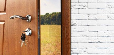 Photo pour La moitié de porte d'entrée s'est ouverte à l'arrière-plan de nature. Poignée de porte, serrure de porte. Sortez à l'extérieur. Ouvrir la porte. Entrée de la maison. Porte au mur de brique blanc, champ et forêt d'été, concept de liberté. - image libre de droit