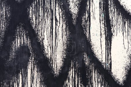 White concrete wall with black paint drips, abstract background