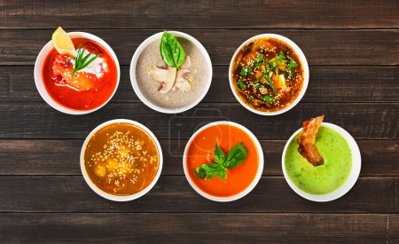 Variety of restaurant hot dishes, healthy food. Japanese miso soup, asian fish soup, russian borscht, english pea soup with bacon, mushroom soup, spanish gazpacho at brown rustic wood, top view