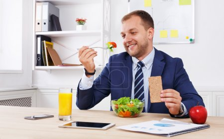 Man has healthy business lunch in modern office interior