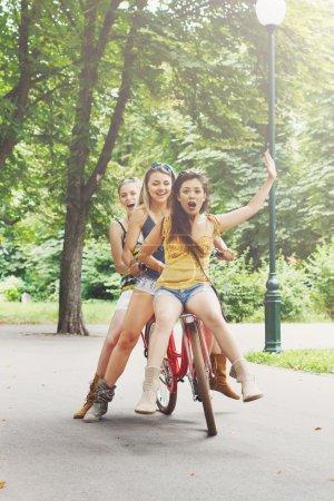 Happy boho chic stylish girls ride together having...