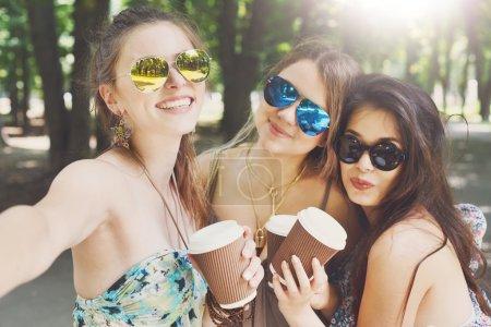 Photo pour Portrait du trois boho de jeune belle filles chic chic dans le parc. Happy sourire des amis dans des lunettes de soleil colorées, s'amuser en plein air. Jolies jeunes femmes boivent du café dans la ville d'été, mode de jeunes - image libre de droit