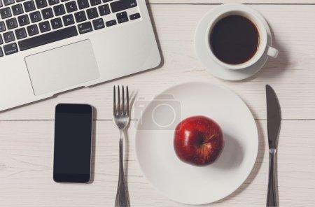 Photo pour Alimentation et concept de manger saine - aucun aliment sauf apple au déjeuner d'affaires au bureau. Vue de dessus de bureau en bois blanc, assiette presque vide, tasse de café americano et coutellerie près de portable et mobile - image libre de droit