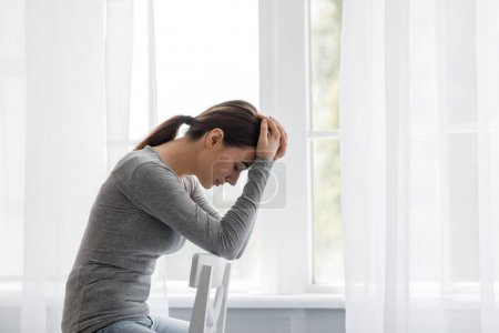 Photo for Unhappy european millennial female sad at home alone, holding her head and sitting on chair, on window background, profile. Lady need professional psychological help. Depression, stress and loneliness - Royalty Free Image