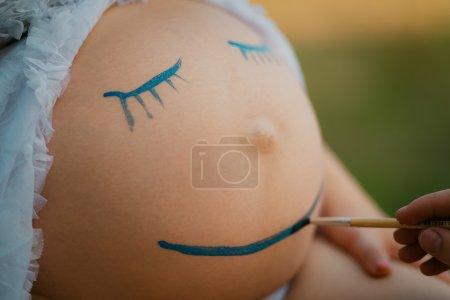 Photo pour Grossesse femme ventre gros plan avec sourire drôle visage dessin - image libre de droit