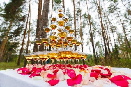 Photo pour Pyramide de verre à cocktail sur la table de fête - image libre de droit