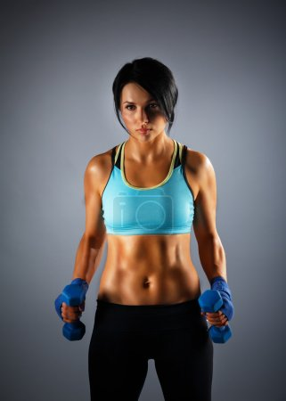 Youmg sportive woman with dumbbells at grey background