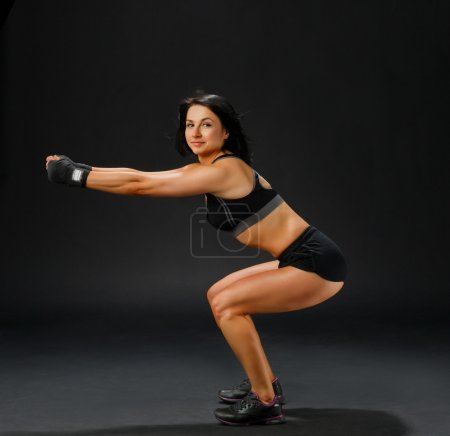 Woman in black fitness suit doing squatting