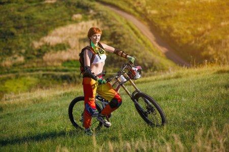 Photo pour Sports d'été extrêmes - jeune femme sportive forte ou sportive posant avec un vélo de montagne de descente en équipement de protection - image libre de droit