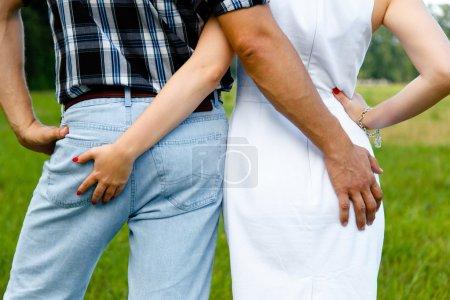 Photo pour Vue de dos masculins et féminins touchent butt - image libre de droit
