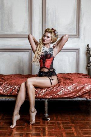 Photo pour Blonge Femme en corset médiéval robe historique et lingerie posant au lit - image libre de droit