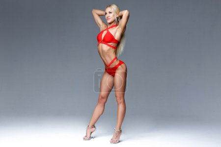 Photo for Sexy young beautiful full body blonde woman posing in red modern bikini swimsuite - Royalty Free Image