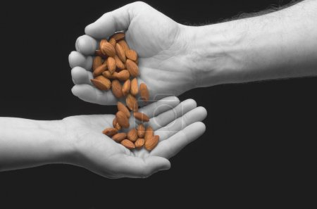 Man and woman's hands sharing almonds on black bac...