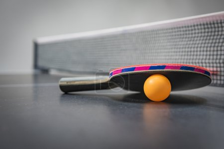 table tennis racket with orange ball