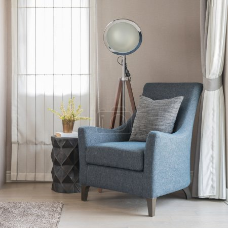 classic blue sofa style with grey pillows and modern lamp on woo