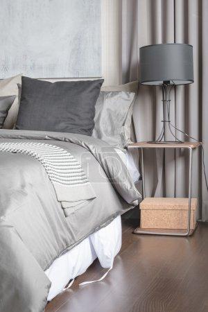 Photo pour Oreiller gris sur lit blanc dans une chambre moderne avec lampe noire sur table en bois - image libre de droit