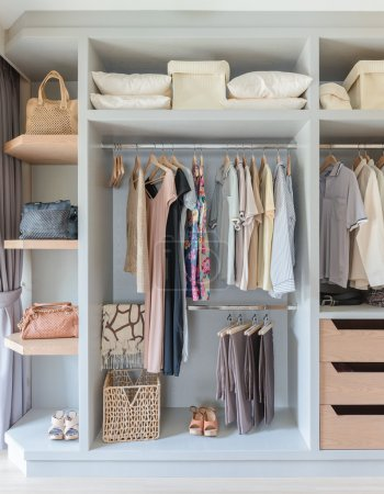 White wardrobe with shirts and pants hanging