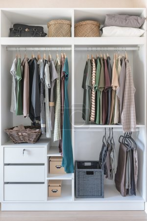 Clothes and dress hanging on rail in white closet