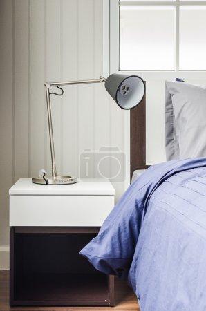 modern lamp on white nightstand in bedroom