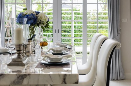 table set in white dinning room with chairs