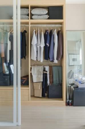 Walk in closet with clothes hanging in wooden wardrobe