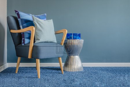 Photo for Wooden chair with blue color pillow on carpet in living room - Royalty Free Image