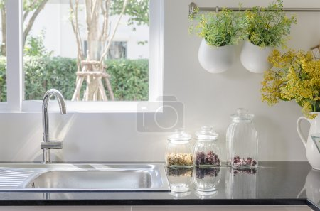 Modern sink on black kitchen counter with vase of ...