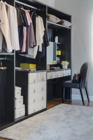 dark color scheme modern walk in closet design with black chair