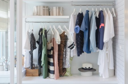 Photo for Clothes hanging in closet with hat at home - Royalty Free Image