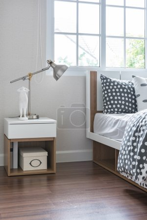 Modern lamp on bedside table with wooden bed
