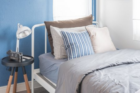 Single white bed with white lamp and blue wall