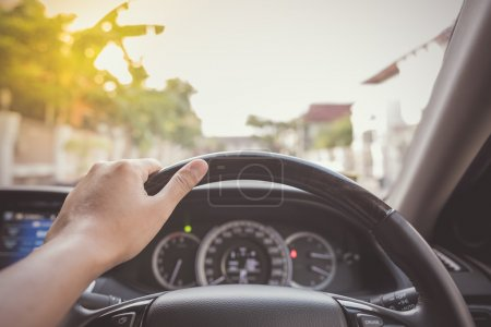 hand of driver on steering wheel of car