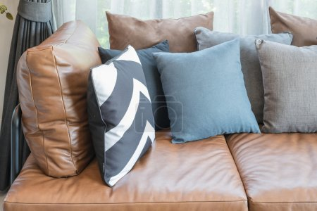 pillows on brown leather sofa