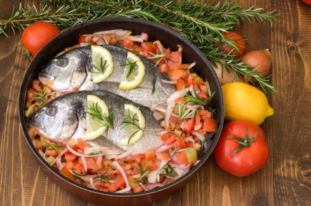 Sea fish with vegetables before baking.