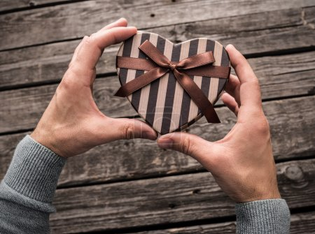 Photo for Heart shaped gift box in male hands. Top view - Royalty Free Image