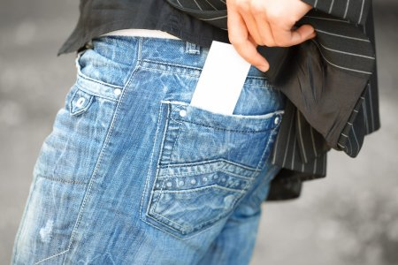 Man in jeans with business card