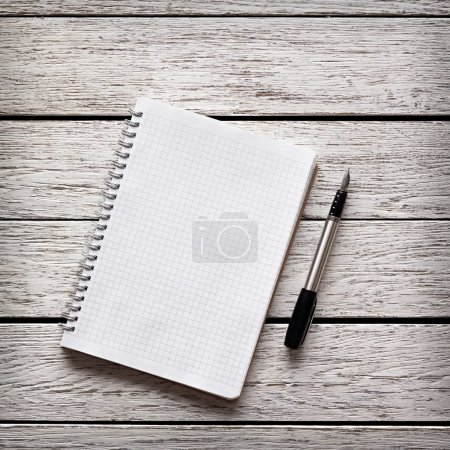 Photo for Blank notepad with a pen on white wooden desk. - Royalty Free Image