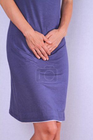Woman with hands holding her crotch close up. Gynecology, period, female healthcare, digestive system, Urinary Tract Infections