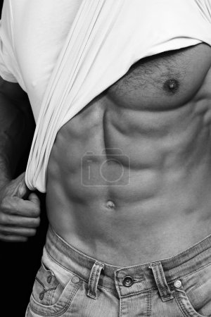 Muscular Men, perfect body, abs, six pack. Strong athletic guy in jeans showing his abs. Bodybuilding, sport, fitness ,workout, active lifestyle concept. Black and white photo