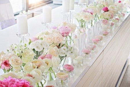 Wedding table decoration.  Ranunculus, roses, candels