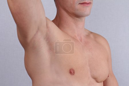 Male Waxing. Muscular male torso, chest and armpit hair removal close up.