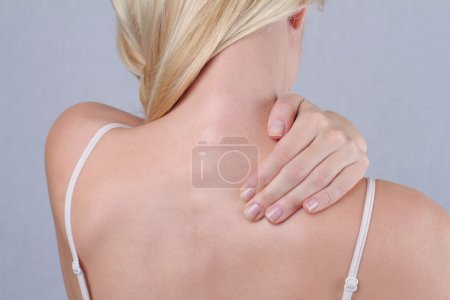 Woman with neck and back pain. Woman rubbing his painful back close up. Pain relief concept