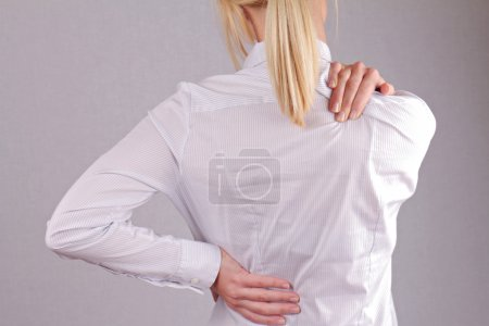 Woman with neck / back pain. Business woman rubbing her painful back close up. Pain relief concept