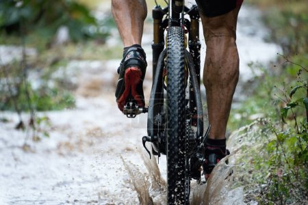 Photo for Mountain biker driving in rain upstream creek - Royalty Free Image