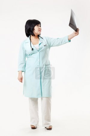 Curvy woman doctor standing considers the results of radiology department, x-ray skull picture outstretched arm, in turquoise medical gown with stethoscope. Asian appearance, dark short hair.