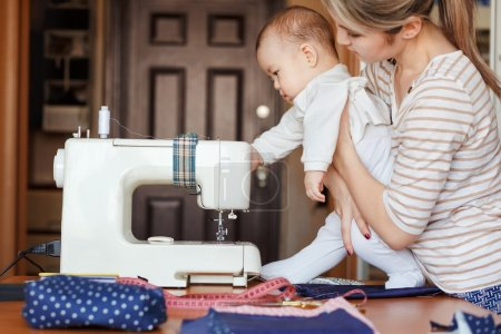 Small child learns new knowledge, along with his mother inspects sewing machine. Work at home, parenting, parents and children, care, babysitter.