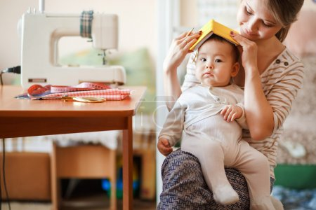 Raising children, child care, baby sitter. Mother and infant at home playing role-playing games. Cute fun parenting.