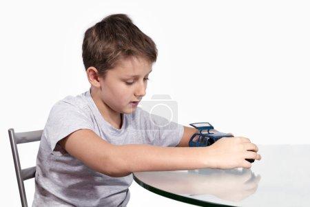Photo pour Garçon caucasien assis à une table en verre, a ouvert la porte arrière voiture bleue et pensé - image libre de droit