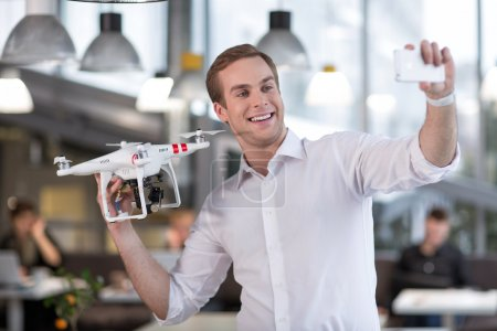 Attractive young guy is photographing with quadrocopter